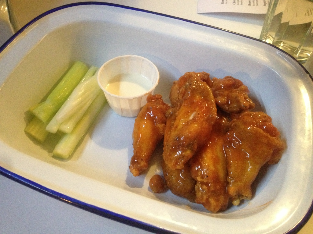 hot buffalo wings with blue cheese dip and celery